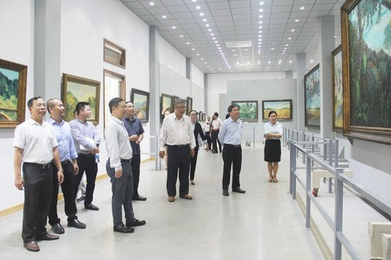 Vice Chairman of the municipal People's Committee, Duong Anh Duc leads a delegation of officials to visit Mr. Bui Van Ngo's exhibition room. (Photo: SGGP)