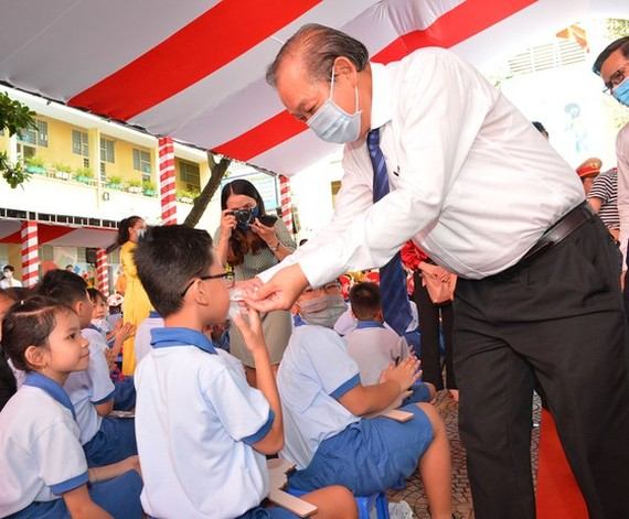 Deputy Prime Minister Truong Hoa Binh helps a student to wear face mask. (Photo: SGGP)