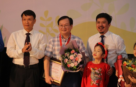 Children author Nguyen Nhat Anh (C) receives the Cricket Knight prize.