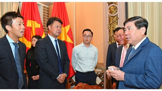 Chairman of the municipal People's Committee Nguyen Thanh Phong (R) receives General Director and Chief Operating Officer of Uniqlo Vietnam, Osamu Ikezoe. (Photo: SGGP)