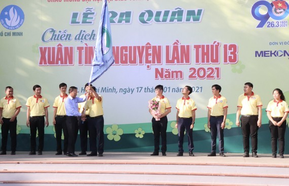 Head of the HCMC Party Committee's Mass Mobilization Commission Nguyen Huu Hiep (L) hands over a flag to students to kick off the campaign. (Photo: SGGP)