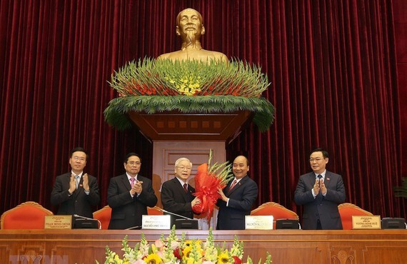 Prime Minister Nguyen Xuan Phuc offers flowers to General Secretary of the Communist Party of Vietnam Nguyen Phu Trong (Photo: VNA)