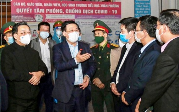 Secretary of Hanoi's Party Committee Vuong Dinh Hue (C) and Hanoi's leaders monitor the implementation of measures to prevent and control Covid-19 in Nam Tu Liem District. (Photo: SGGP)