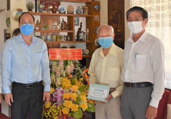 Deputy Secretary of the HCMC Party Committee Nguyen Ho Hai (L) visits Hero of Labor, Pharmacist Tran Van Nhieu. (Photo: SGGP)