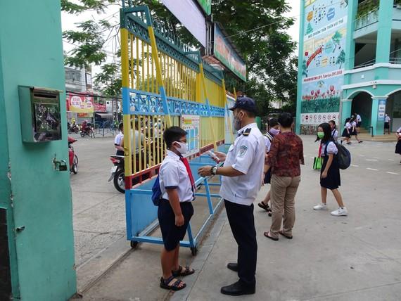 Học sinh Trường Tiểu học An Hội (quận Gò Vấp) được đo thân nhiệt ngay tại cổng trường