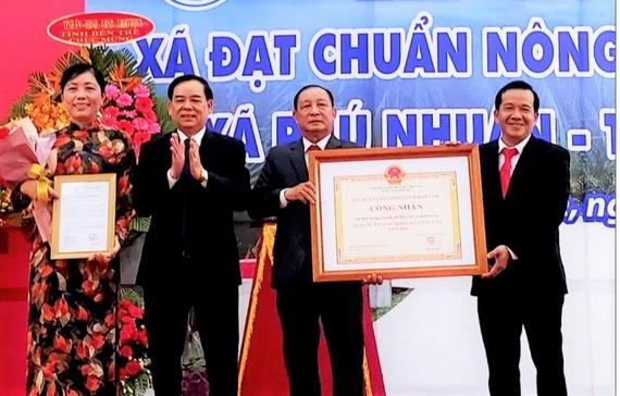 Chủ tịch UBND tỉnh Bến Tre Trần Ngọc Tam (bên trái, thứ 2) trao bằng công nhận xã nông thôn mới nâng cao cho lãnh đạo xã Phú Nhuận