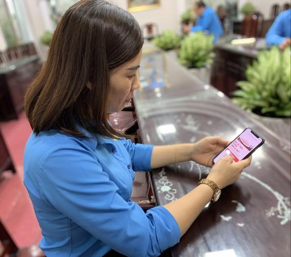 """Người lao động tham gia cuộc thi """"Công nhân, viên chức, người lao động với Ngày hội non sông"""" trên điện thoại di động"""
