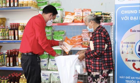 Chủ tịch Hội Chữ thập đỏ TPHCM Trần Trường Sơn giúp người dân chọn hàng tại Phiên chợ nhân đạo tại huyện Nhà Bè