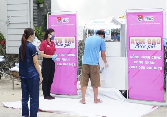 """Thành niên công nhân tại khu lưu trú nhận gạo từ """"máy ATM"""""""
