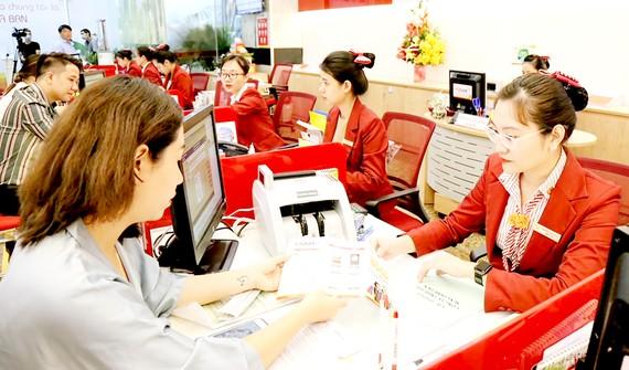 Hoạt động giao dịch tại một ngân hàng ở TPHCM. Ảnh: PHAN LÊ