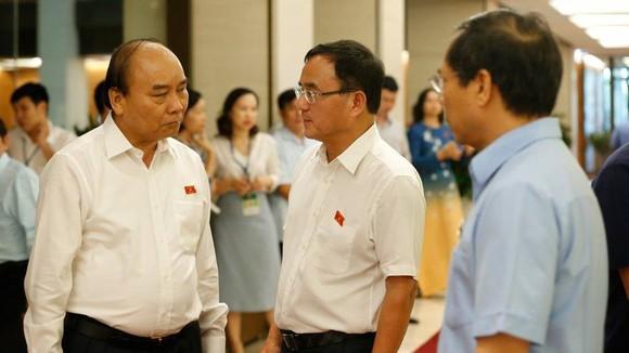 Thủ tướng Nguyễn Xuân Phúc trao đổi với các ĐBQH ngày 13-6. Ảnh: QUANG PHÚC