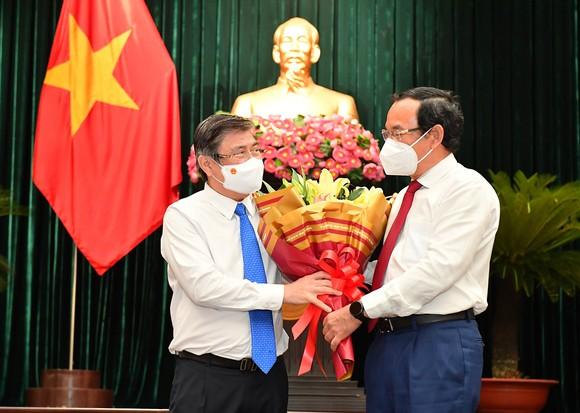 Bí thư Thành ủy TPHCM Nguyễn Văn Nên tặng hoa cho đồng chí Nguyễn Thành Phong tại kỳ họp thứ hai HĐND TPHCM khóa X, ngày 24-8. Ảnh: VIỆT DŨNG
