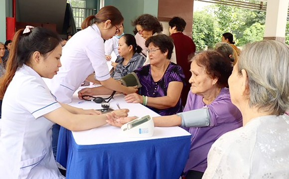 Young medical workers provide checkup to elderly people (Photo: SGGP)