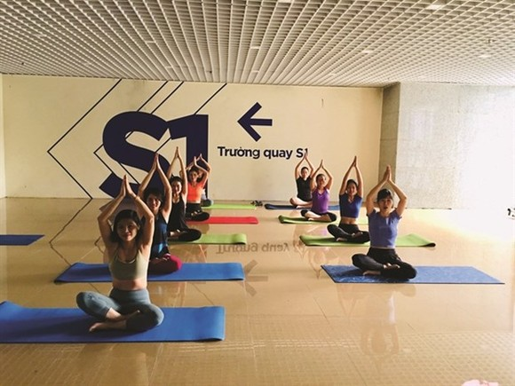 Staff of the VTC Television practise yoga during a break. (Photo: VNA)