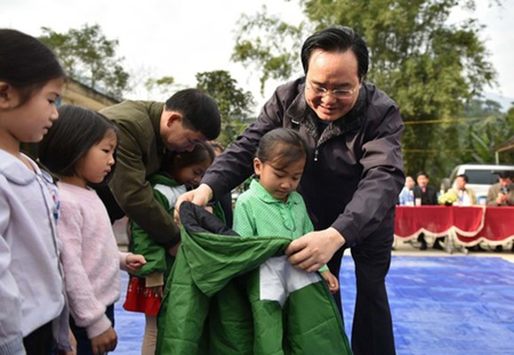 Minister Phung Xuan Nha is delivering warm clothes to poor children. (Photo: SGGP)