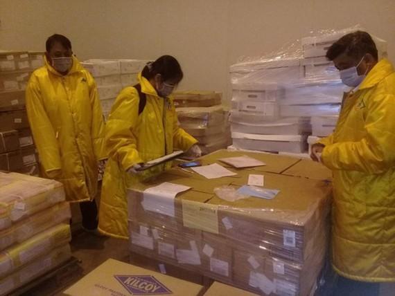 Inspectors check imported frozen food (Photo: SGGP)