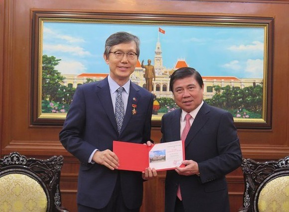 Chairman of the Ho Chi Minh City People's Committee Nguyen Thanh Phong (R) presents the city's insignia to outgoing Republic of Korea (RoK) Consul General Lim Jae Hoon (Photo: VOH)