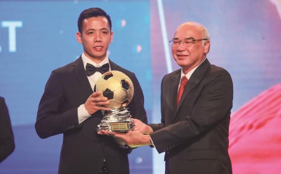 Head of the Propaganda and Training Board Mr. Phan Nguyen Nhu Khue hands over golden ball to football player Nguyen Van Quyet