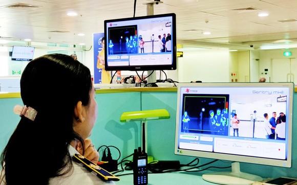 Nhân viên kiểm tra thân nhiệt hành khách nhập cảnh vào Sân bay Tân Sơn Nhất