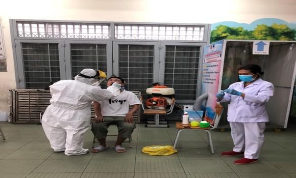 Các bác sĩ Trung tâm Y tế quận 10 đang lấy mẫu phết mũi họng cho bệnh nhân