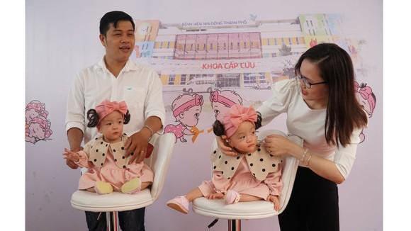 Cặp song sinh cùng ba mẹ trong ngày xuất viện