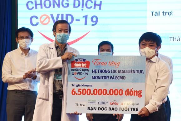 Ông Lê Thế Chữ, Tổng biên tập báo Tuổi Trẻ TPHCM trao bảng tượng trưng món quà bạn đọc báo gửi tới Bệnh viện Bệnh Nhiệt đới TPHCM Ảnh: DUYÊN PHAN