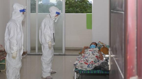 Nhân viên y tế chăm sóc cho bệnh nhân tại Bệnh viện dã chiến và thu dung điều trị Covid-19 số 3. Ảnh: HOÀNG HÙNG