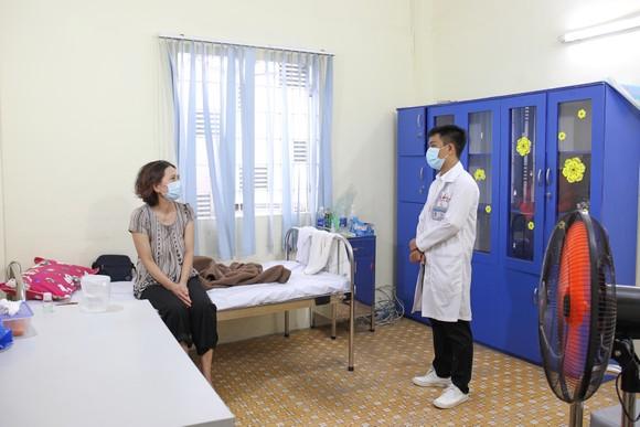 Nhân viên y tế thăm hỏi bệnh nhân đang điều trị tại bệnh viện. Ảnh: HOÀNG HÙNG