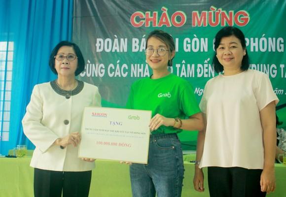 Bà Lý Việt Trung, Phó Tổng Biên tập Báo SGGP (bên phải) cùng đại diện Công ty TNHH Grab trao hỗ trợ 100 triệu đồng cho bà Nguyễn Thị Thu Hà, Giám đốc Trung tâm Võ Hồng Sơn. Ảnh: NGUYỄN TRANG