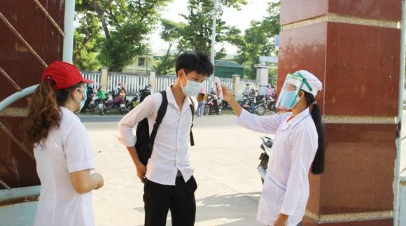 Thí sinh thực hiện đeo khẩu trang, đo thân nhiệt, rửa tay sát khuẩn trước khi vào phòng thi. Ảnh: NGUYỄN TRANG