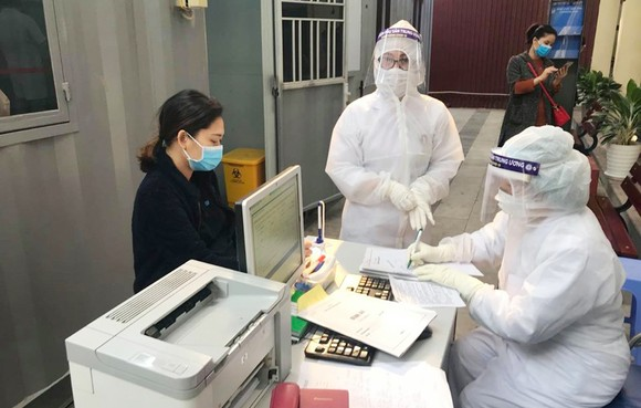"""Nhân viên y tế làm thủ tục thăm khám cho người bệnh tại khu vực phòng khám """"dã chiến"""" của Bệnh viện Phụ sản Trung ương. Ảnh: ncov.moh.gov.vn"""