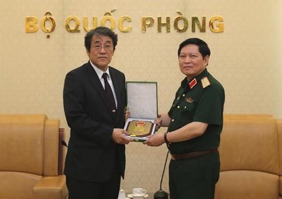國防部長吳春歷大將(左)向日本駐越南特命全權大使梅田邦夫閣下贈送紀念品。(圖源:互聯網)