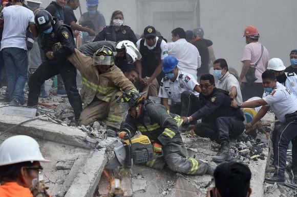 眾多居民被困在廢墟下面,救援工作正緊張進行。(圖源:AFP)