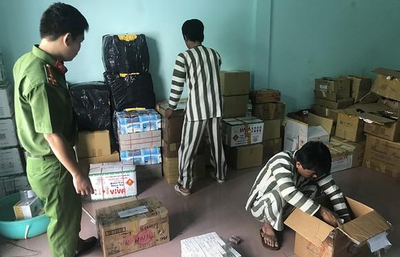 不久前在假藥生產案中被拘捕的疑犯在市公安廳幹部的 監察下點算贓物。