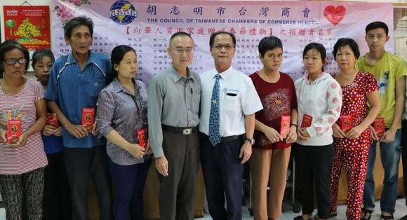 本報編委兼編輯部主任范興與台商會會長鄭文忠向第五郡華人貧困家庭贈送禮物。