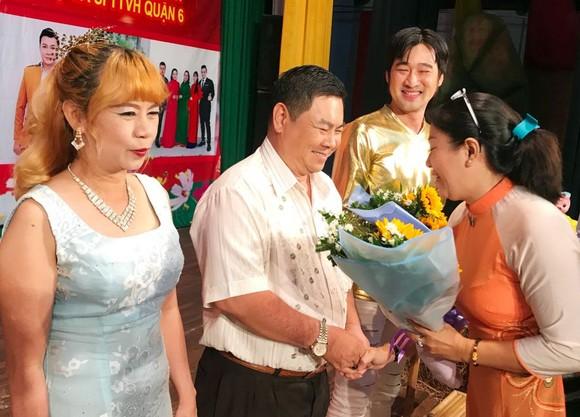 第六郡婦聯會主席梁青竹向華人熱心人士贈花致謝。