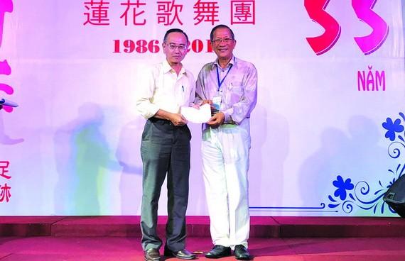 陳志華團長向本報編輯部主任 范興(左)轉交善款。