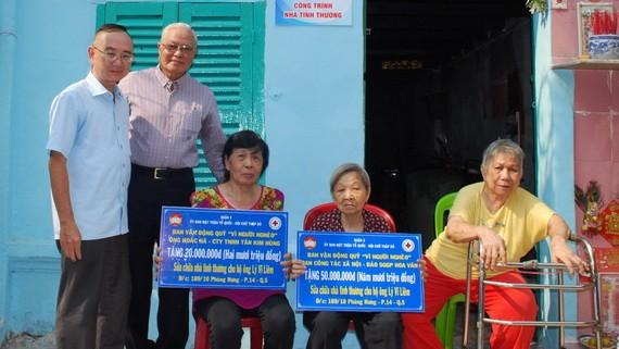 本報編委兼編輯部主任范興(左)和華企呂永雄在轉 交儀式上向戶主象徵贈送贊助修建溫情屋經費數目牌子。