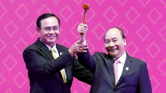 阮春福總理(右)從泰國總理巴育手中接過象征東盟輪值主席國身份的木槌。(圖源:VGP)