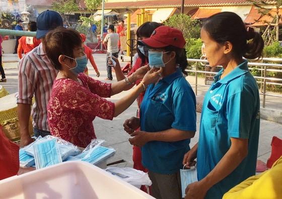 華人商販應氏蓮(左一)正在向消費者派發口罩。