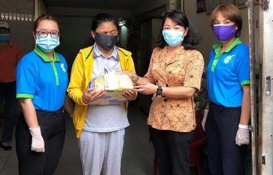 第六郡婦聯會主席梁氏菁竹(右二)向一名華人貧困者贈送禮物。