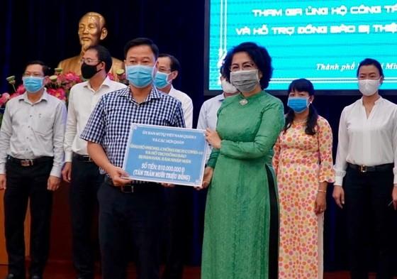 市越南祖國陣線委員會主席蘇氏碧珠接受第五郡領導的抗疫善款。