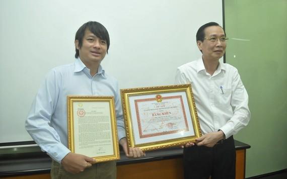 市人委會常務副主席黎清廉親自轉發表揚信和獎狀給黃俊英(左)。(圖源:高昇)