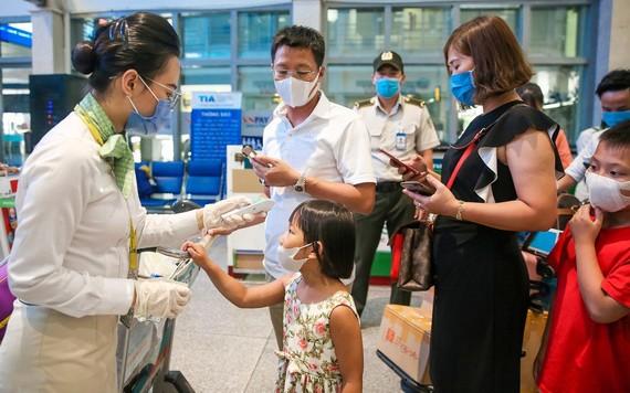 乘務員為乘客檢測體溫。(圖源:Zing)