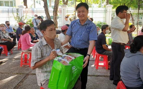 第五郡越南祖國陣線委員會主席黎晉才送禮物給貧困戶。