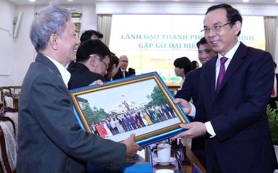 黨中央書記、市委書記阮文年(右)向僑胞贈送紀念品。