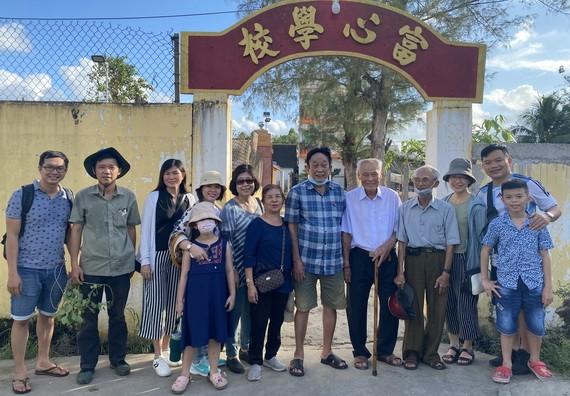 陸進義老師與鄉親和學生們在母校前合影。