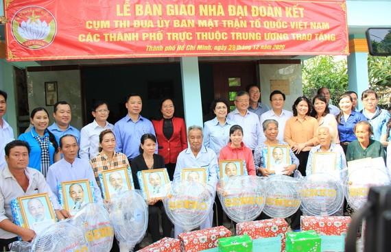 市越南祖國陣線委員會領導向貧困戶贈送胡伯伯肖像及禮物。