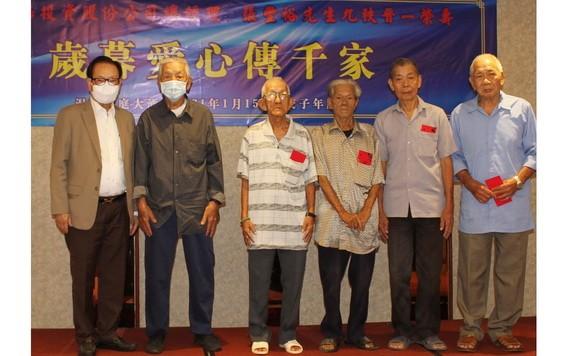 時代廣場投資股份公司總經理張豐裕先生(左一)向華人貧困同胞贈送賀年紅包。