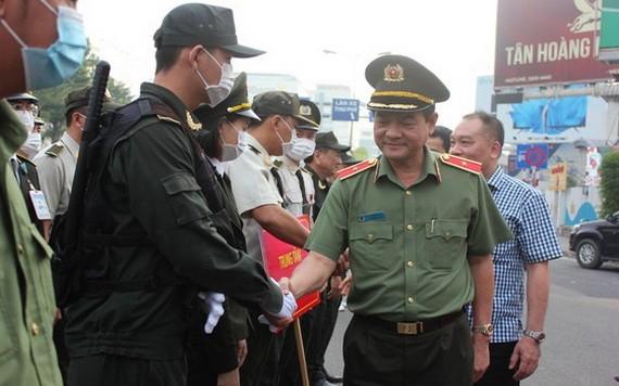 市公安廳長黎鴻南少將與新山一機場執勤武警親切握手,互致問候。(圖源:志石)